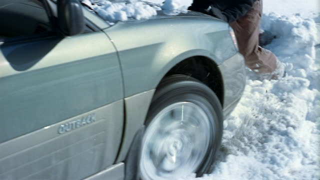 vidéos et rushes de medium shot man pushing car stuck in snowbank / vermont - panne de voiture