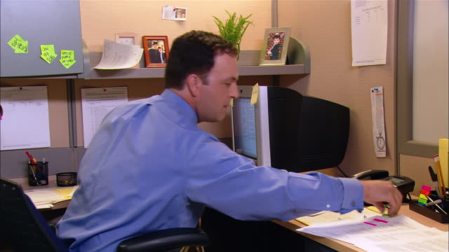 Medium shot man putting away pens and straightening up papers on his desk in cubicle