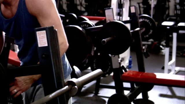 vídeos de stock, filmes e b-roll de medium shot man putting large weight on barbell/ shaky pan up man looking at camera - equipamento para exercícios