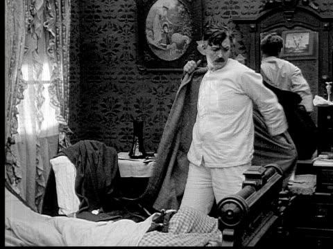 1913 b/w medium shot man putting on bathrobe and grabbing long cane in bedroom / usa  - 1913 stock videos & royalty-free footage