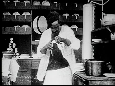 1914 b/w medium shot man putting on wig and bandana and checking disguise in ship galley - galeere stock-videos und b-roll-filmmaterial
