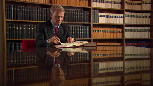 vidéos et rushes de medium shot man reading at table in law library with reflection in table/ man smiling/ man reading/ rome - avocat juriste