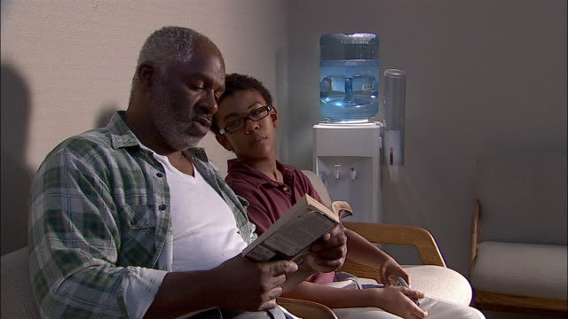 medium shot man reading book in doctor's office waiting room as boy plays with handheld video game / boy laughing at man as he holds book at a distance - handheld video game stock videos & royalty-free footage