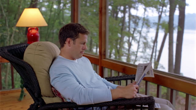 medium shot man reading newspaper in porch of lakehouse / looking at view of lake - clarkesville stock videos & royalty-free footage