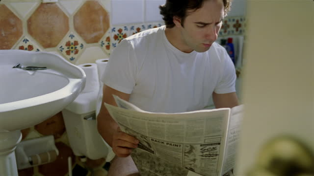 medium shot man reading newspaper on toilet - toilet stock videos and b-roll footage