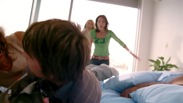 Medium shot man reading on bed / three women running into room and jumping on top of him / South Africa