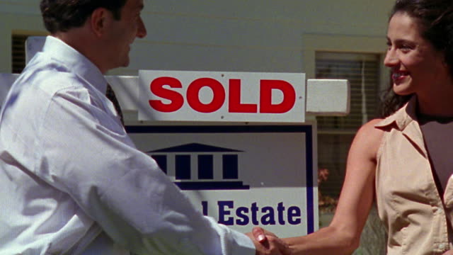 """medium shot man real estate agent attaching shaking woman's hand with """"sold"""" real estate sign in background - real estate sign stock videos & royalty-free footage"""