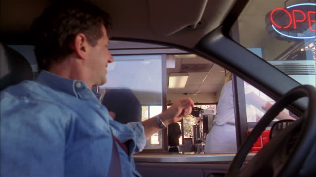 medium shot man receiving change and food order from employee in fast food drive-thru window - schnellkost stock-videos und b-roll-filmmaterial