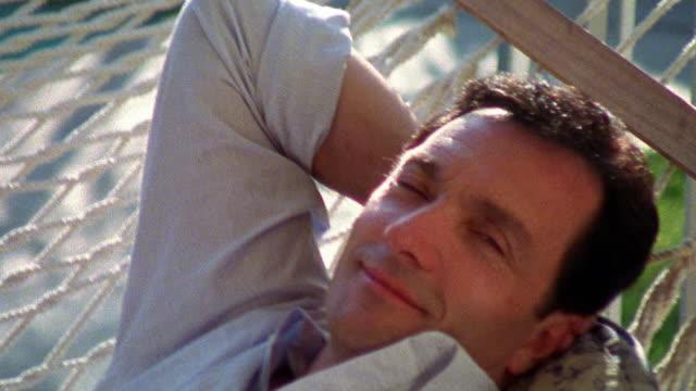 vídeos y material grabado en eventos de stock de medium shot man relaxing on hammock - hamaca