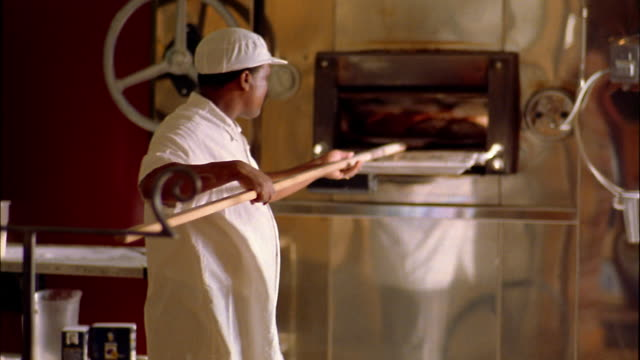 medium shot man removing loaves of bread from oven and sliding them onto cooling rack / seattle, washington - bread stock videos and b-roll footage