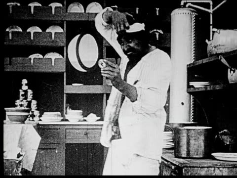 1914 B/W Medium shot Man removing wig and bandana in ship galley