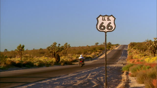 vidéos et rushes de medium shot man riding motorcyle on highway w/route 66 highway sign in foreground - route 66