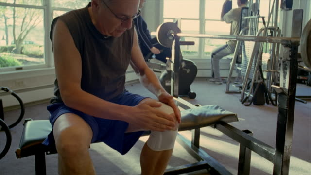 medium shot man rubbing bandaged knee while working out in gym/ solebury, pennsylvania - rubbing stock videos & royalty-free footage