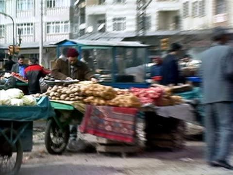 Medium shot Man selling potatos at produce stand in market/ Turkey