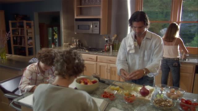 Medium shot man separating eggs as boys do homework at kitchen counter / woman in background at kitchen sink