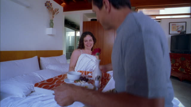 vídeos de stock e filmes b-roll de medium shot man serving breakfast on tray to woman in bed and eating w/her - sentar se