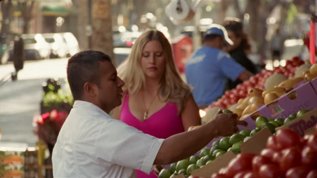 Medium shot man shopping at outdoor fruit market as flirty woman walks over and reaches in front of him/ California