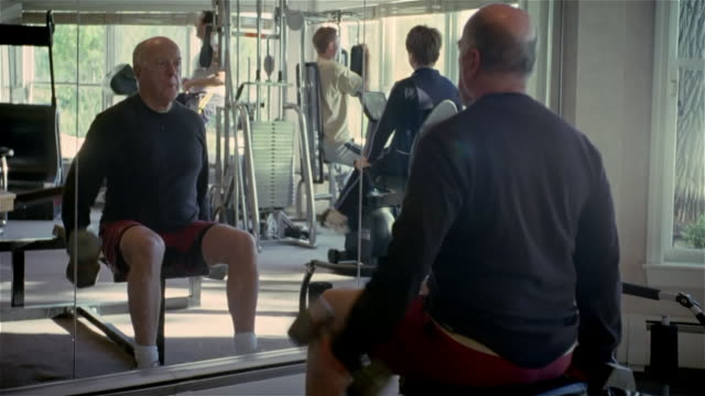 medium shot man sitting and lifting barbells in mirror at gym/ solebury, pennsylvania - weights stock videos & royalty-free footage