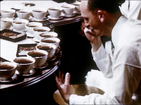1954 medium shot man sitting and tasting coffee as cups spin around on conveyor belt / audio - tasting stock videos and b-roll footage