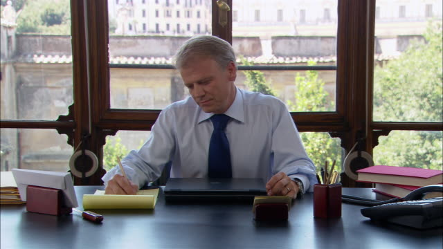 vídeos de stock, filmes e b-roll de medium shot man sitting and thinking at desk/ man smiling and writing/ rome - com as mãos na cabeça