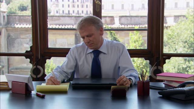 vidéos et rushes de medium shot man sitting and thinking at desk/ man smiling and writing/ rome - se tenir la tête entre les mains
