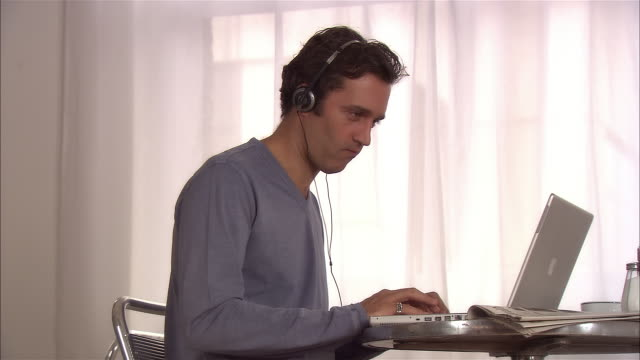 medium shot man sitting at cafe table typing on laptop / listening to headphones / drinking tea - nodding head to music stock videos & royalty-free footage
