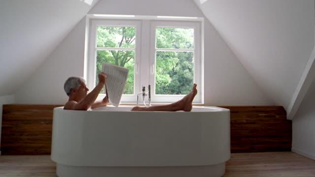 medium shot man sitting in bathtub reading newspaper w/windows and view of trees in background - badewanne stock-videos und b-roll-filmmaterial