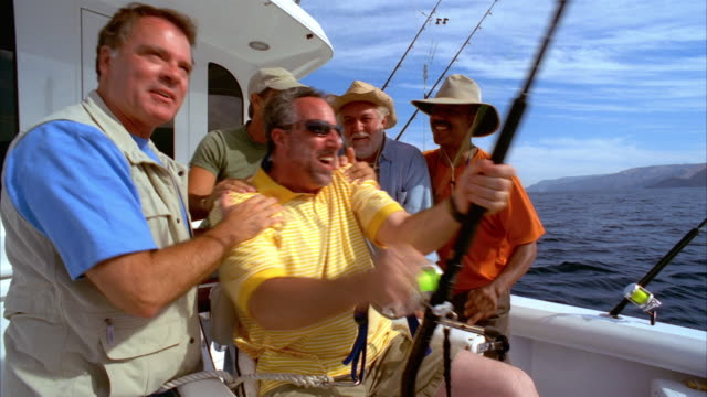 vídeos de stock, filmes e b-roll de medium shot man sitting in fighting chair on yacht and struggling with fish on his line as his friends surround him/ california - 50 anos