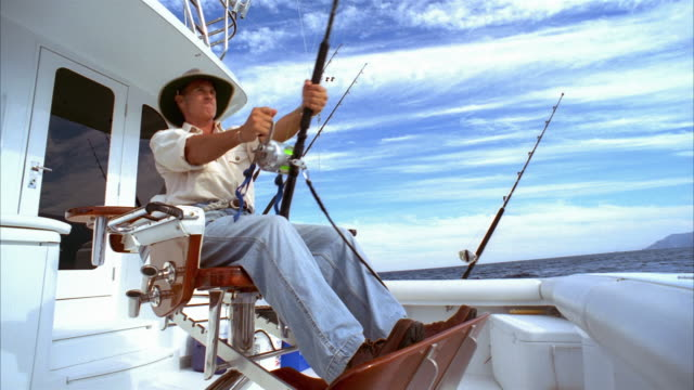 Medium shot man sitting in fighting chair on yacht and struggling with fish on his line as friend comes to join him/ close up hands on fishing rod/ California