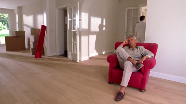 medium shot man sitting in red chair thinking / movers carrying boxes into large room w/wood floors - ラグ点の映像素材/bロール