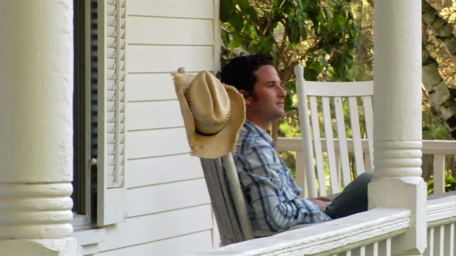medium shot man sitting in rocking chair on porch and waving - nachbar stock-videos und b-roll-filmmaterial