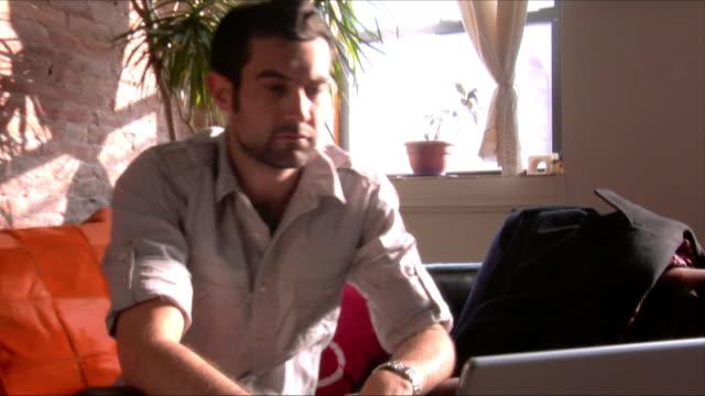 stockvideo's en b-roll-footage met medium shot man sitting on couch and looking at laptop/ new jersey - hanenkam haardracht