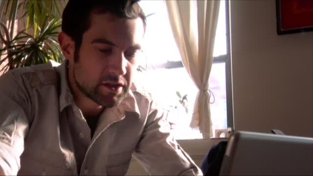 stockvideo's en b-roll-footage met medium shot man sitting on couch, typing on laptop/ new jersey - hanenkam haardracht