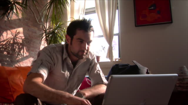 medium shot man sitting on couch, typing on laptop/ new jersey - sideburn stock videos and b-roll footage
