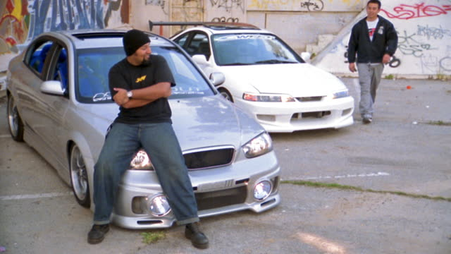 vídeos de stock e filmes b-roll de medium shot man sitting on hood of car w/arms crossed / man gets out of second car and both greet each other - sentar se