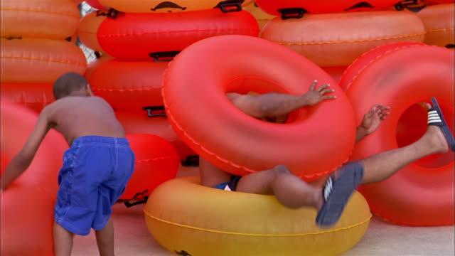Medium shot man sitting on inner tube / young boy piling inner tubes on top of man