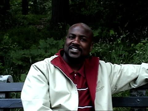 stockvideo's en b-roll-footage met medium shot man sitting on park bench, talking and touching tongue to nose/ brooklyn - menselijke neus