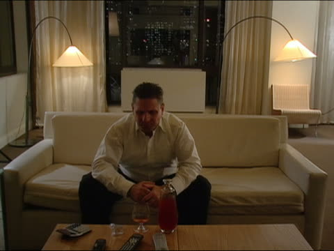 medium shot man sitting on sofa / drinking snifter of brandy / relaxing - brandy snifter stock videos & royalty-free footage