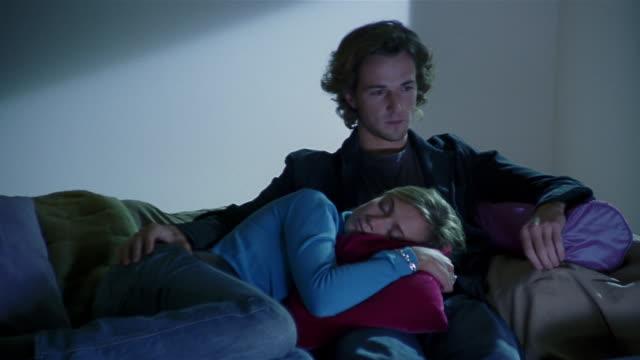 Medium shot man sitting on sofa watching television / woman asleep lying on his lap