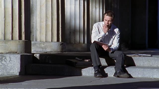 Medium shot man sitting on steps and comtemplating paper