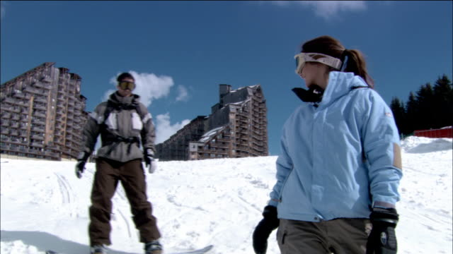 medium shot man snowboarding up to woman / couple smiling and kissing - ski goggles stock videos & royalty-free footage