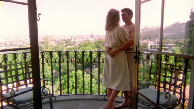 medium shot man standing on balcony with towel tied around waist / hugging woman in robe - waist stock videos & royalty-free footage