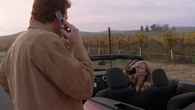 Medium shot man standing outside red convertible, talking on cell phone, as woman sits in car/ Napa Valley, California
