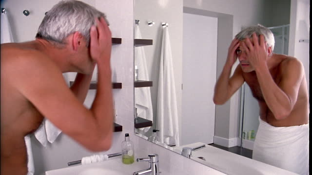 Medium shot man standing w/hands resting on bathroom sink looking in mirror / fixing hair and walking away