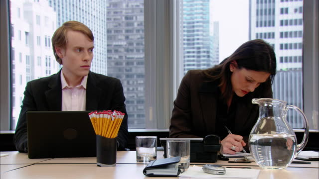 Medium shot man staring at woman in flirtatious way in office board room/ woman turning to look/ man spraying breath freshener in mouth/ New York, New York
