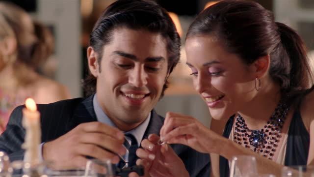 Medium shot man surprising woman with ring during meal at formal restaurant