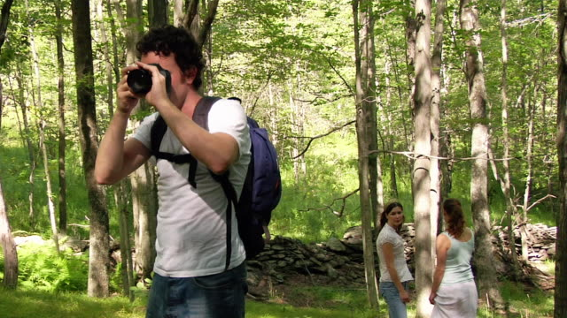 medium shot man taking photograph in woods / continuing hike with two women - maschio con gruppo di femmine video stock e b–roll