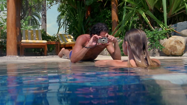 medium shot man taking picture of woman in pool - 2004年点の映像素材/bロール