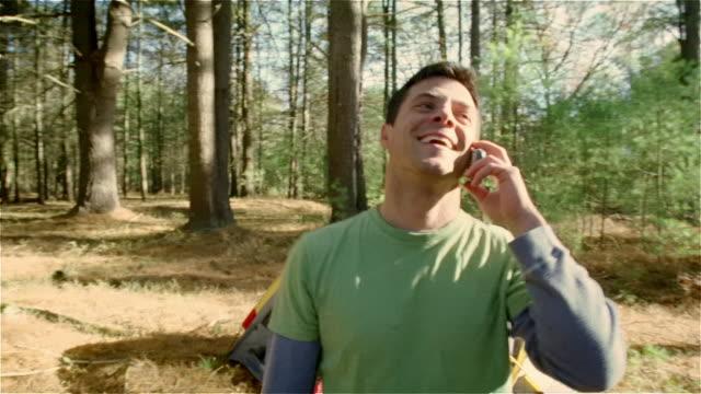 vídeos y material grabado en eventos de stock de medium shot man talking on cell phone while camping/ new york state - tienda de campaña