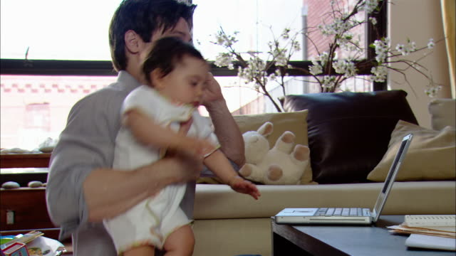 medium shot man talking on cell phone with baby on his lap / baby reaching for laptop on coffee table - coffee table stock videos & royalty-free footage
